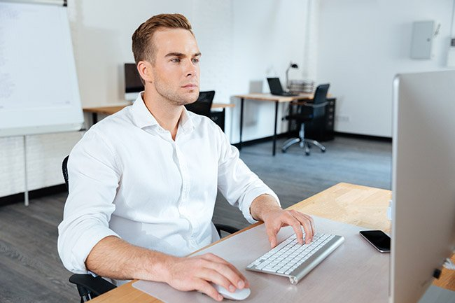 Businessman sitting in office and using computer